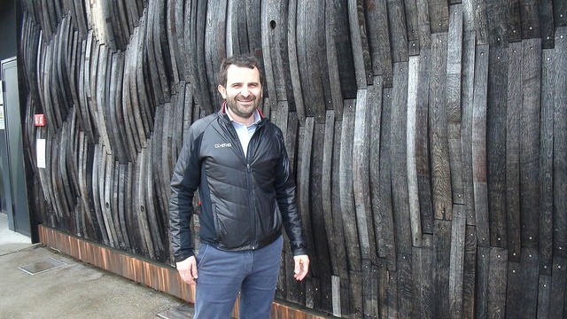 Achille Boroli in front of his winery where the walls are covered in old barrels