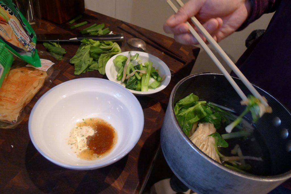 """""""Melting"""" the flavouring sachets and taking the greens and mushrooms from the broth pot."""